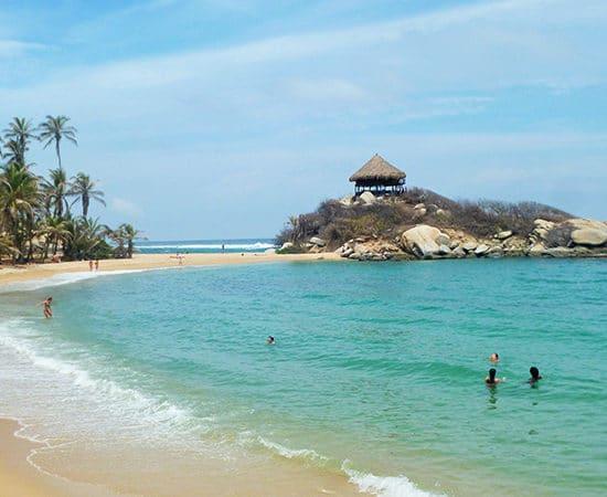 colombie tayrona plage eau turquoise palmiers rochers cahutte