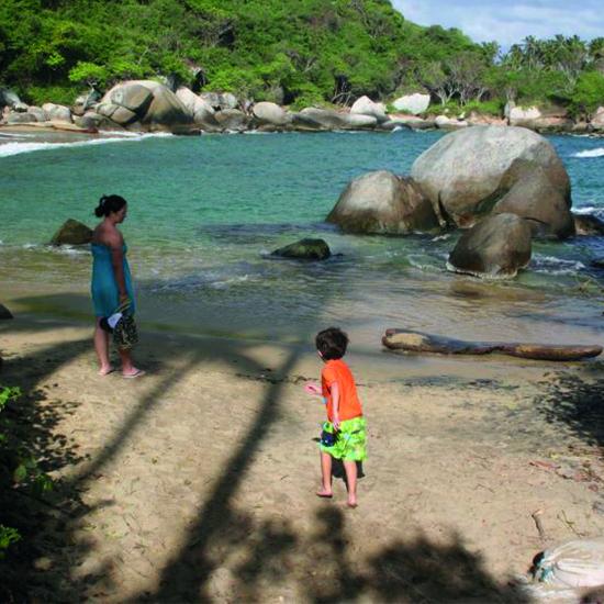 colombie tayrona plage enfant rochers eau turquoise forêt